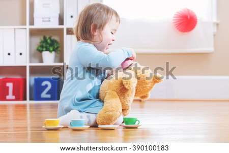 Happy toddler girl have tea with her teddy bear  - stock photo