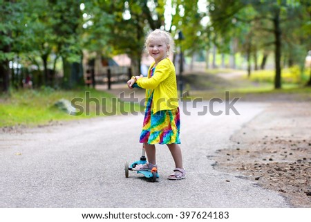 Happy toddler girl in beautiful dress riding with scooter in the park. Cute little kid enjoying sport outdoors on summer day. Active children vacation concept. - stock photo