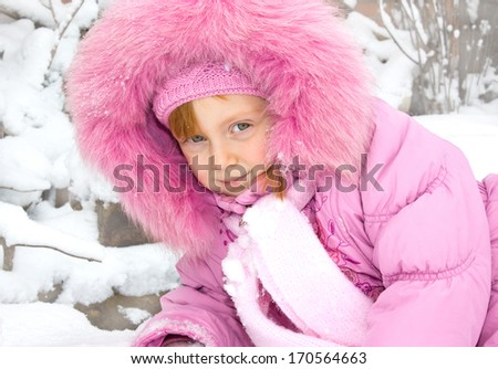 Happy toddler girl looking straight in the camera at the playground in winter.  - stock photo