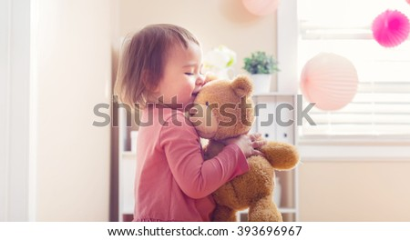 Happy toddler girl playing with her teddy bear at house - stock photo