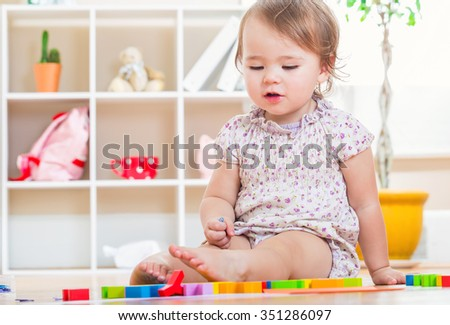 Happy toddler girl playing with her toys inside her house - stock photo