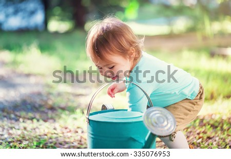 Happy toddler girl smiling and playing outside with a watering can  - stock photo