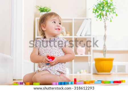 Happy toddler girl smiling and playing with her toys in her house - stock photo