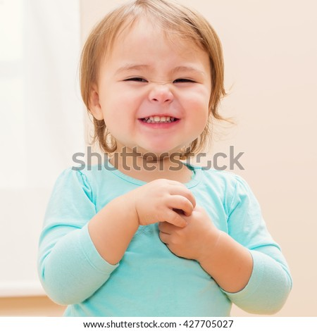 Happy toddler girl with a giant smile in her house - stock photo