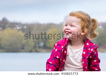 Happy toddler sticking tongue out next to lake  - stock photo