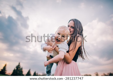 Happy together. Beautiful young mother and her son having fun at cloudy field - stock photo