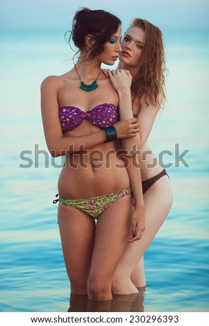 Happy together concept. Beautiful couple of models with perfect arty make-up in bikini at the seaside. Long wet hair and waterproof decorative cosmetics. Summer evening. Vintage style. Outdoor shot - stock photo