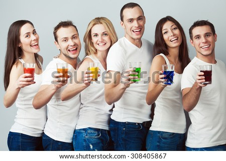 Happy together concept. Company of healthy boys and girls in white t-shirts, sleeveless shirts and blue jeans standing with vegetable, fruit juice posing over gray background. Urban style. Studio shot - stock photo