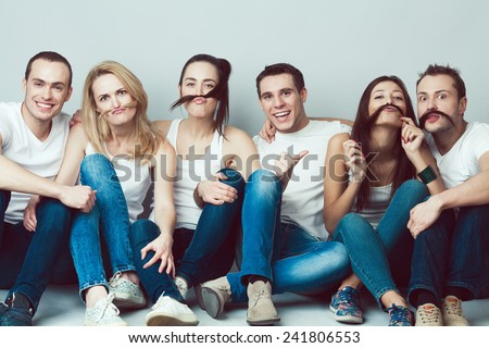 Happy together concept. Group portrait of healthy boys and girls in white t-shirts, sleeveless shirts and blue jeans sitting and posing over gray background. Copy-space. Urban style. Studio shot - stock photo
