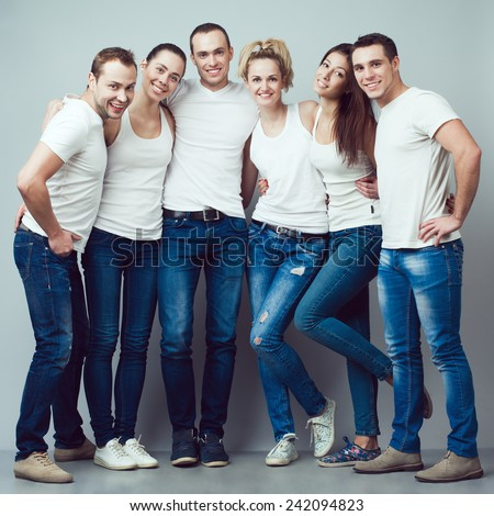 Happy together concept. Group portrait of healthy boys and girls in white t-shirts, sleeveless shirts and blue jeans standing and posing over gray background. Urban style. Studio shot - stock photo