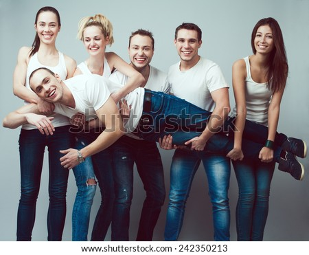 Happy together concept. Group portrait of healthy boys and girls in white t-shirts, sleeveless shirts and blue jeans holding friend in hands and posing over gray background. Urban style. Studio shot - stock photo