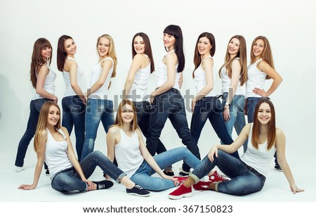 Happy together concept. Group portrait of healthy girls in white t-shirts and blue jeans sitting and posing over white background. Copy-space. Urban style. Studio shot - stock photo