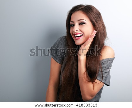Happy toothy laughing brunette young woman with hand near face on blue background - stock photo
