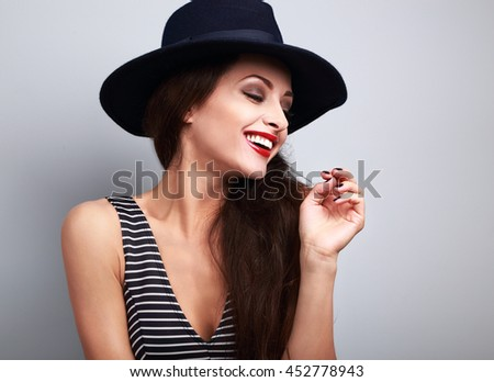 Happy toothy laughing female model profile in black elegant hat on blue background - stock photo