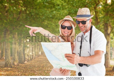 Happy tourist couple using map and pointing against walkway along lined trees in the park - stock photo
