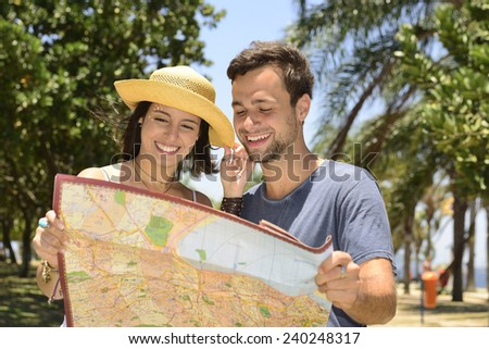 Happy tourist couple with map - stock photo
