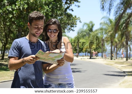 Happy tourist couple with map doing sightseeing with copy space - stock photo