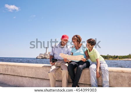 Happy tourist family on holidays, during vacation journey in Cuba. Hispanic grandpa, grandma and grandson traveling in Havana reading a city map on the Malecon - stock photo