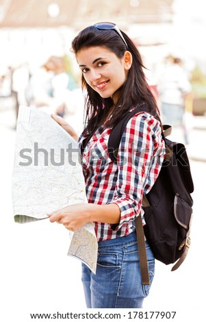 Happy tourist with map in her hand, smiling to the camera. - stock photo