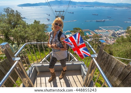Happy tourist woman holding an English flag. On background the cable car that leads to Gibraltar Rock. Gibraltar is a British colony that is located at southern end of Iberian Peninsula. - stock photo