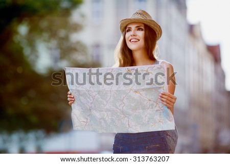 Happy tourist woman on vacation with map visiting city - stock photo