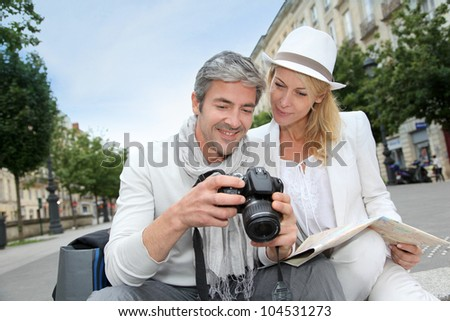 Happy tourists looking at pictures on camera screen - stock photo