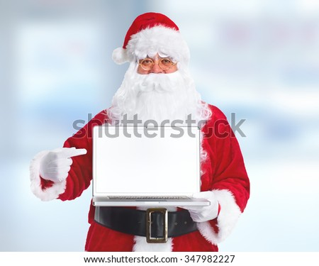 Happy traditional Santa Claus with laptop computer over blue background. - stock photo