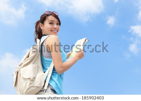Happy travel woman look map and look to you with sky background, asian - stock photo