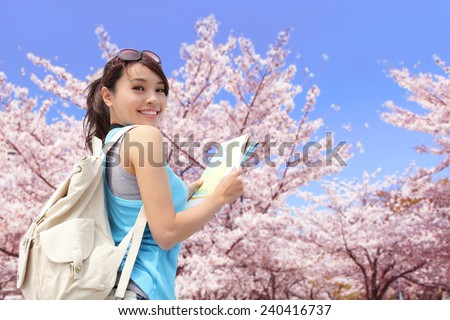 Happy travel woman look map and smile with sakura cherry blossoms tree on vacation while spring, asian - stock photo