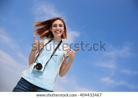 Happy travel woman smile to you and show thumb up with sky background, caucasian beauty - stock photo
