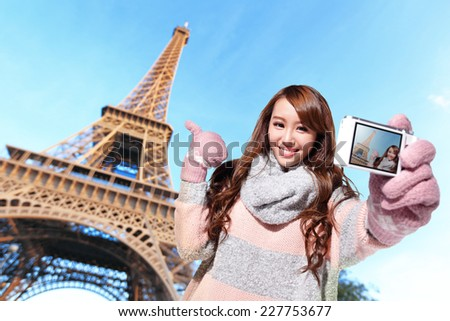 Happy travel woman take a selfie by camera with eiffel tower in Paris with blue sky - stock photo