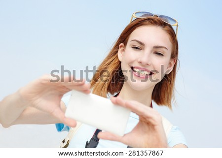 Happy travel woman take a selfie picture by smart phone with sky background, caucasian beauty - stock photo