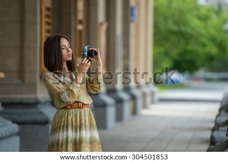 Happy traveler girl making photo of historical building with retro camera on city street - stock photo