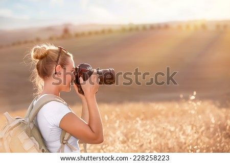 Happy traveler girl photographing ripe wheat field in bright sun rays, autumn harvest season, interesting profession, travel and tourism concept - stock photo