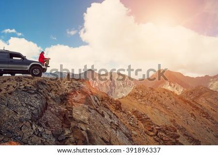 Happy Traveler man sitting on his car on mountains top. 4x4 travel trekking  - stock photo