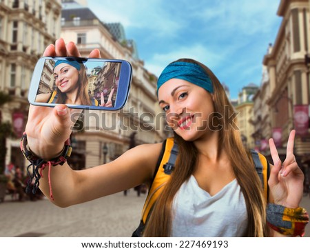 Happy traveler woman is taking selfie - stock photo