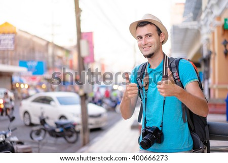 Happy traveling. Young smiling man with backpack and camera showing thumbs up on asian street. - stock photo