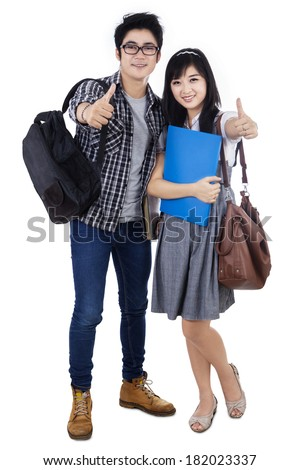 Happy trendy college students with bags and books, showing thumbs-up at camera, - stock photo