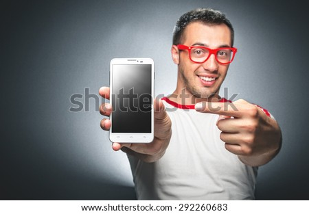 Happy trendy young man showing blank screen of his mobile phone - smartphone space for your text - stock photo