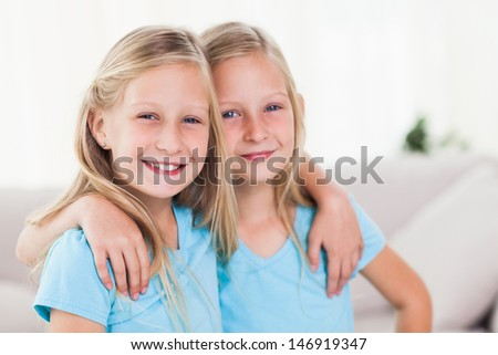 Happy twins embracing each other in the living room - stock photo