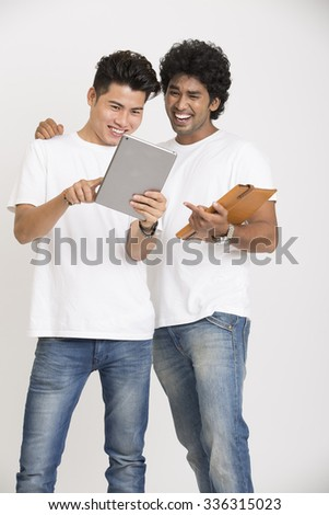 Happy two college students using digital tablet over white background - stock photo