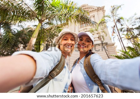 happy two female travellers taking selfie together - stock photo