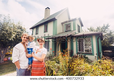 "Happy Ukrainian family dressed in ethnic costumes on the background of their new house. Young parents with their child. Ukrainian traditional clothes is primarily embroidered shirt - ""vyshyvanka"". - stock photo"