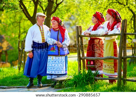 happy ukrainian family, dressed in national costumes, talking on the street - stock photo