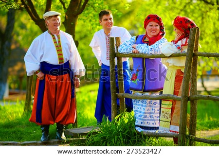 happy ukrainian family in traditional costumes talking near the wooden fence - stock photo