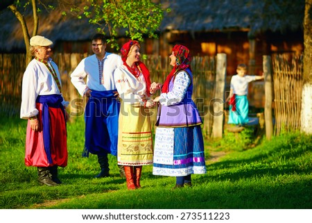 happy ukrainian family in traditional costumes talking outdoor - stock photo