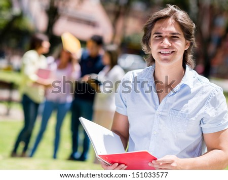 Happy university student at the campus with a notebook  - stock photo