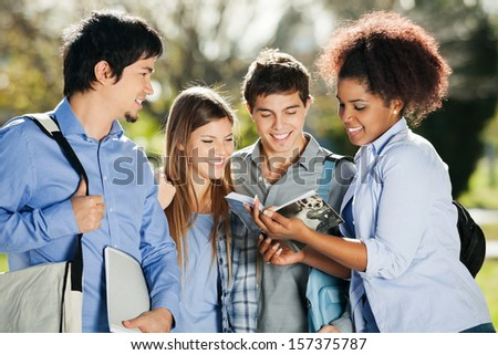 Happy university students reading book together in campus - stock photo