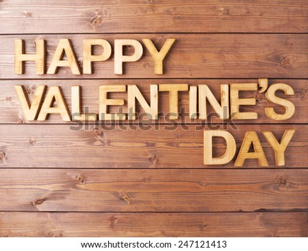 Happy Valentine's Day card made with the block letters over the wooden surface - stock photo
