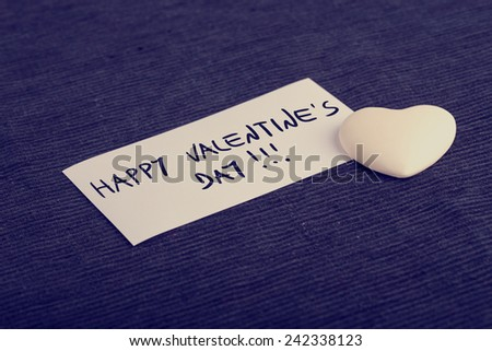 Happy Valentine's day handwritten on a card with a white heart lying on a black background for a Valentines greeting, retro effect faded look. - stock photo